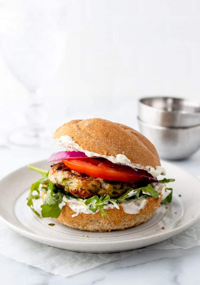 Up close shot of turkey burger on a bun with tzatziki, arugula, tomato and onion slices with glass and bowls in background