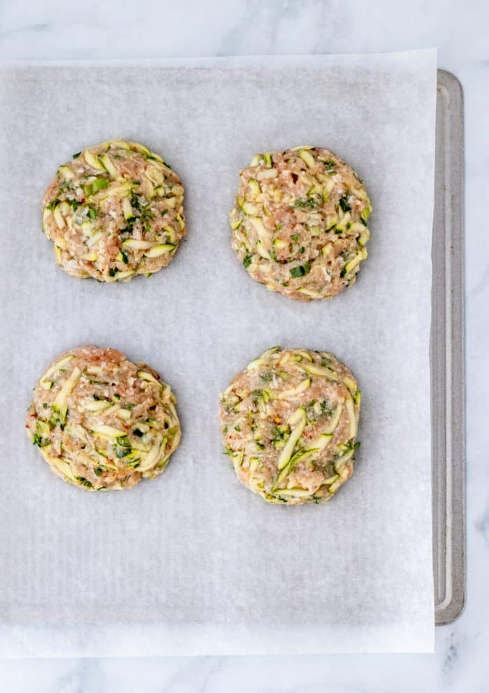 Uncooked burger patties on a parchment paper lined baking sheet