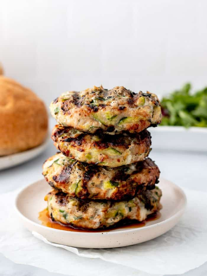 A stack of turkey burgers on a plate next to buns and arugula