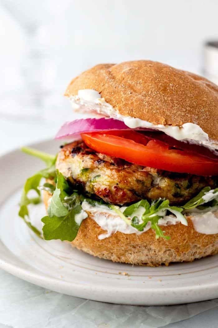 Up close shot of turkey burger on a bun with tzatziki, arugula, tomato and onion slices