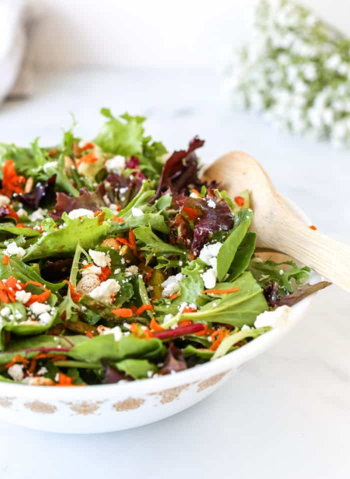 Spring mix salad in a large serving bowl.