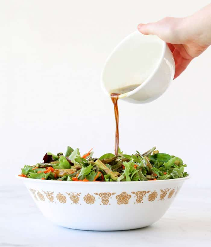 Pouring balsamic dressing over the salad in a white serving bowl