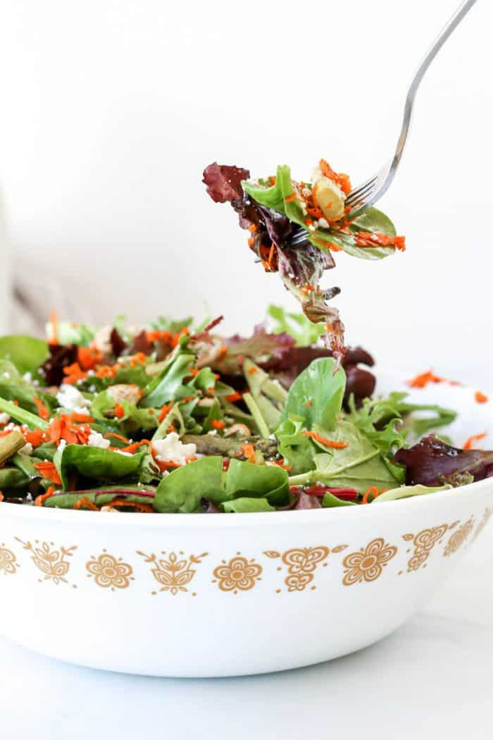 A fork picking up some of the salad from a serving bowl.