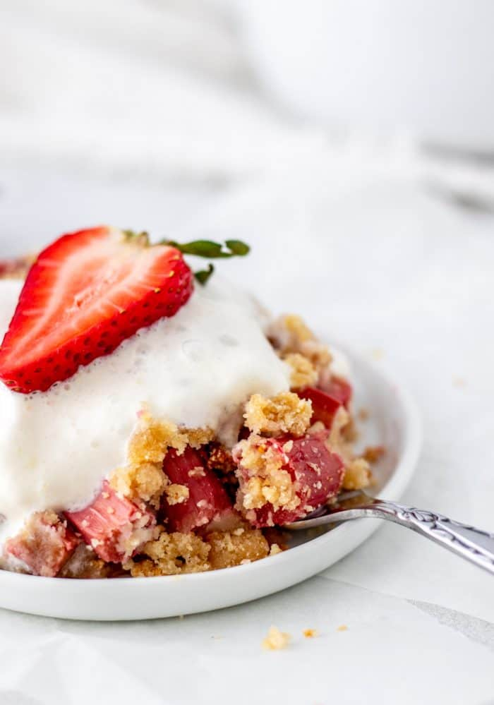 Fruit crumble served in a bowl with a spoon.