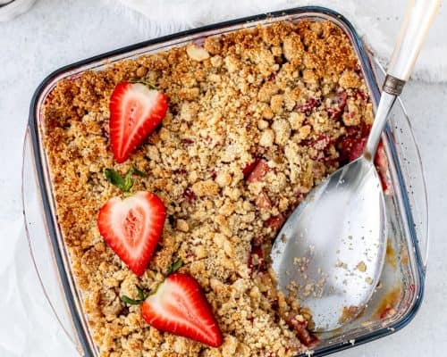 Strawberry rhubarb crumble in a glass dish with a serving spoon,