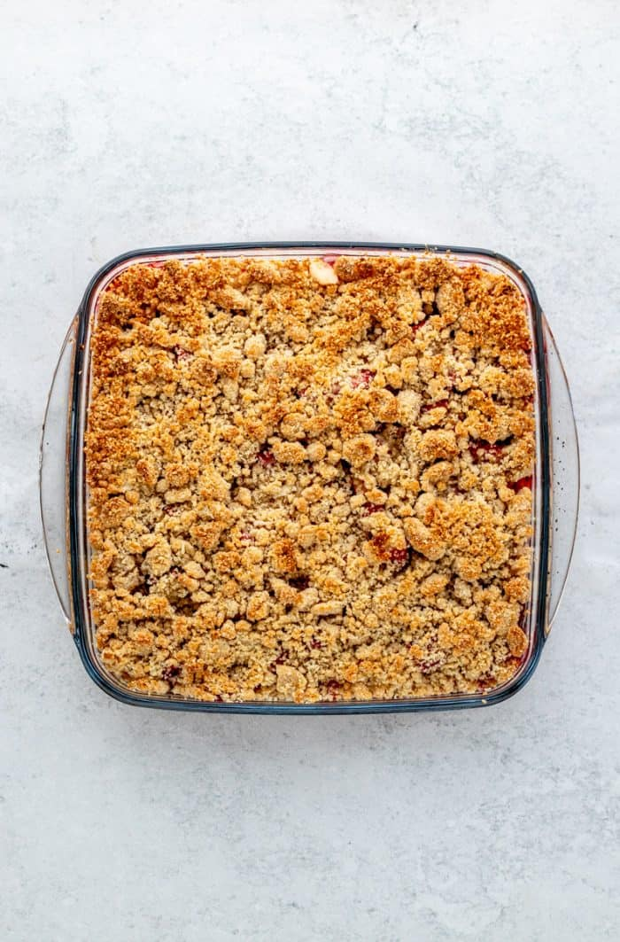 The baked strawberry rhubarb crumble in a glass dish.