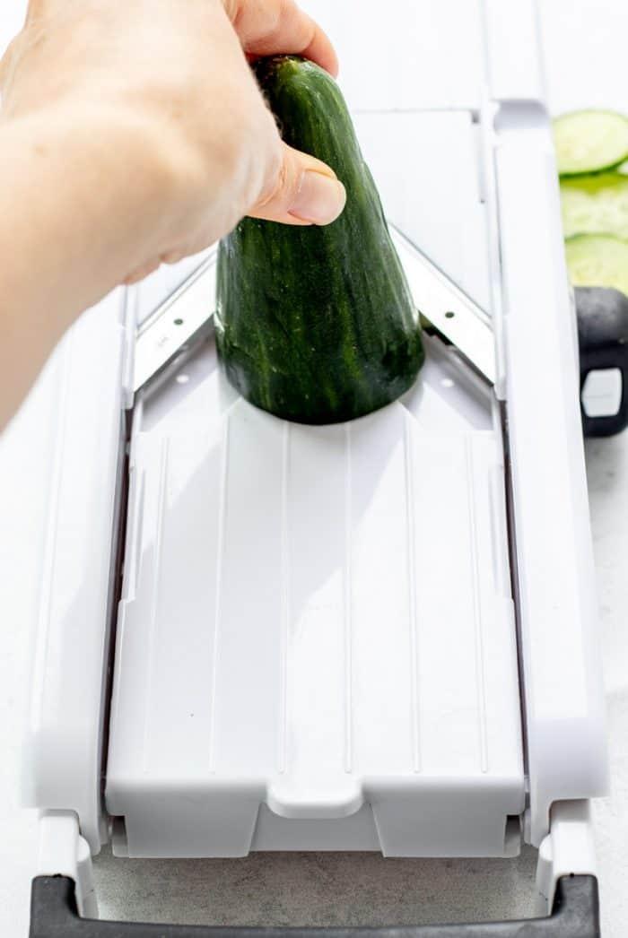 Slicing a cucumber with a mandoline.