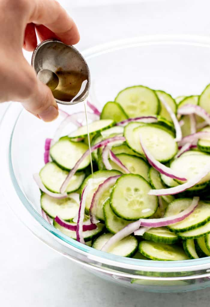 Pouring the rice vinegar over the salad.