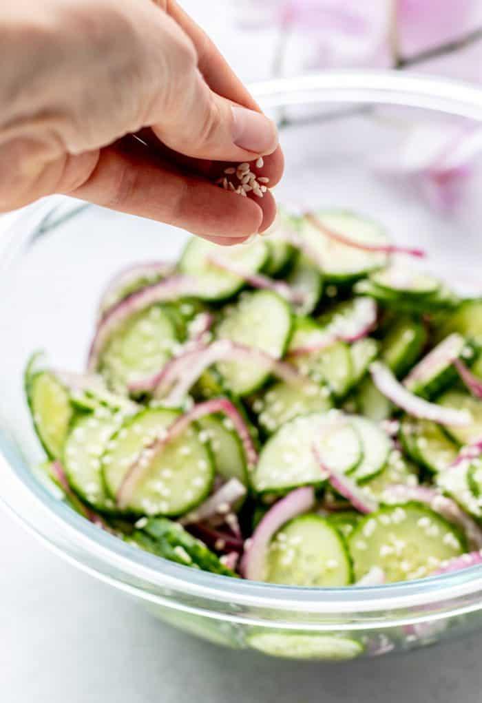 Sprinkling sesame seeds over the salad.