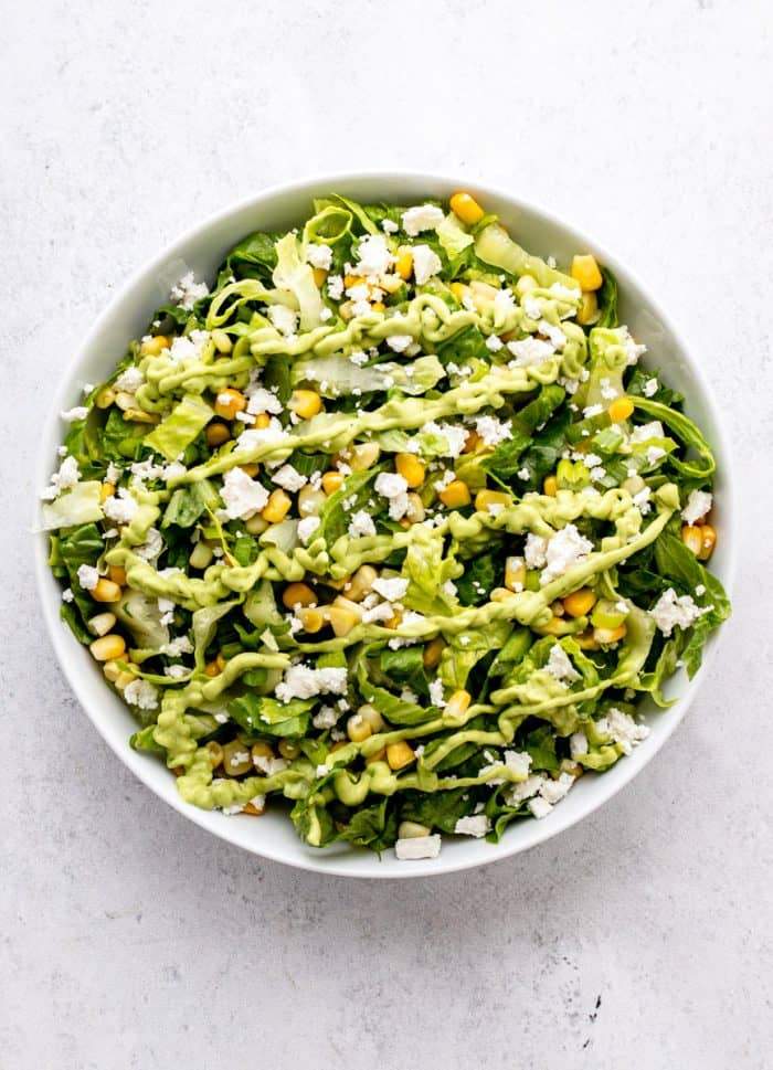 A green salad in a bowl with green goddess dressing.