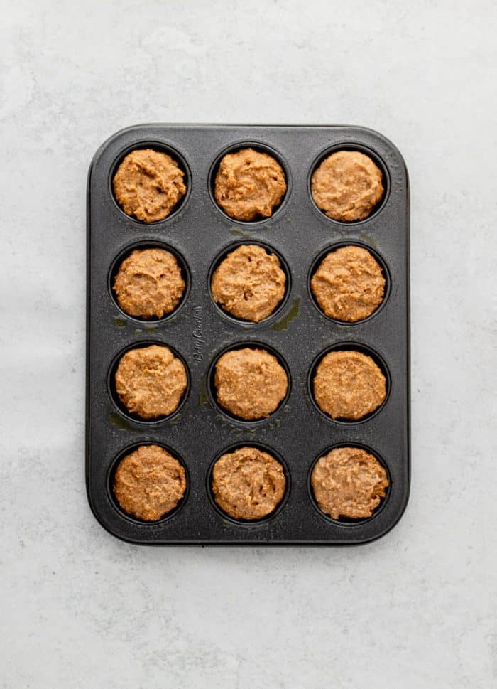 The muffin batter in a muffin tin.