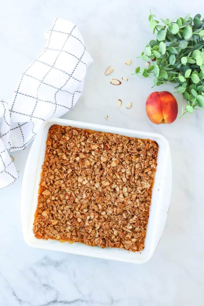 A baked peach crumble in a white baking dish.