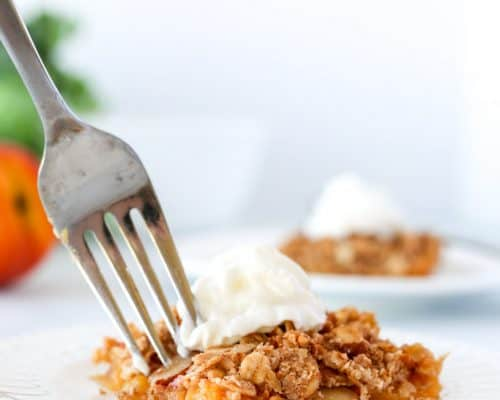 Peach crumble on two white plates with one being eaten with a fork.