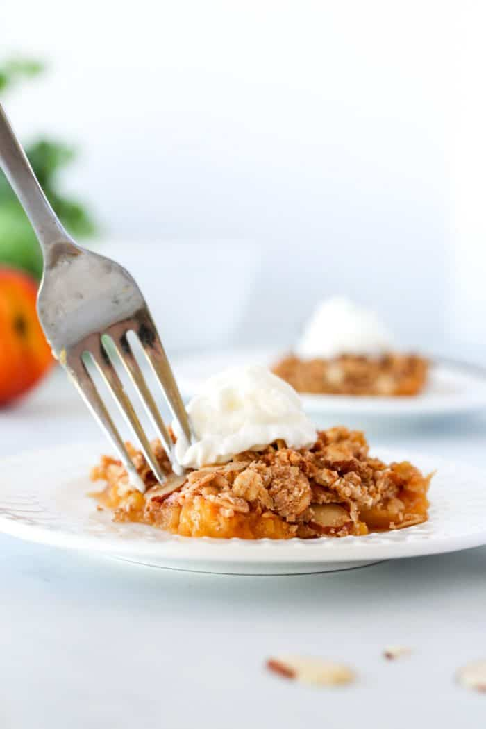 A fork picking up a piece of crumble from a white plate.