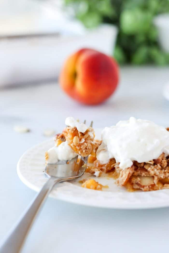 Peach crumble topped with cream.