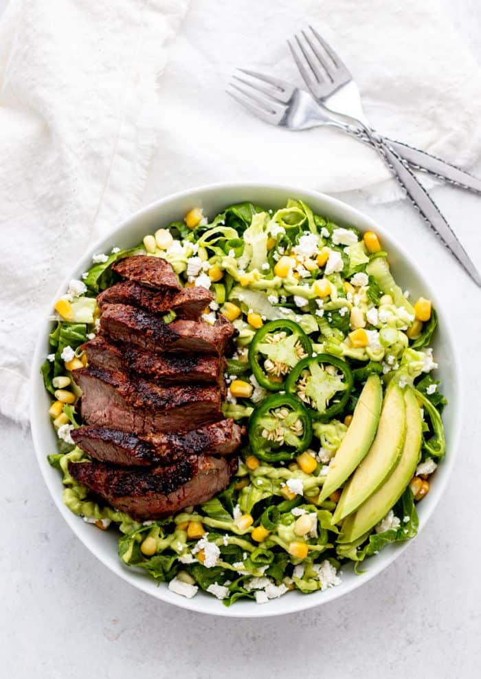 Steak salad in a bowl next to two forks.