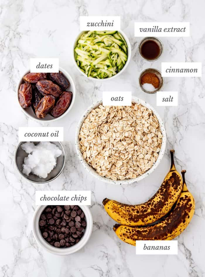 ingredients for zucchini cookies on marble background with labels