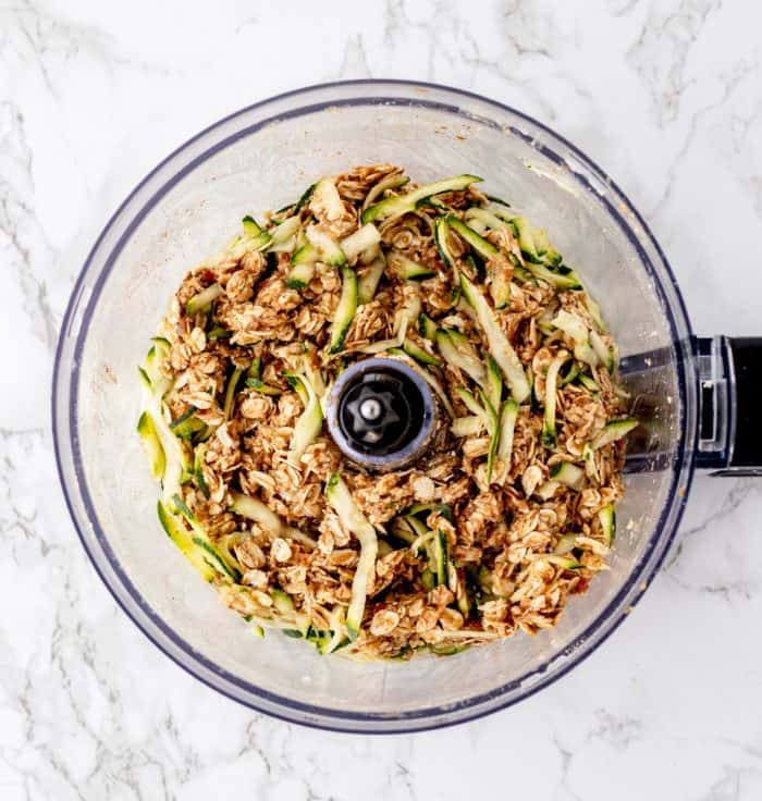 Shredded zucchini added to cookie mixture in food processor