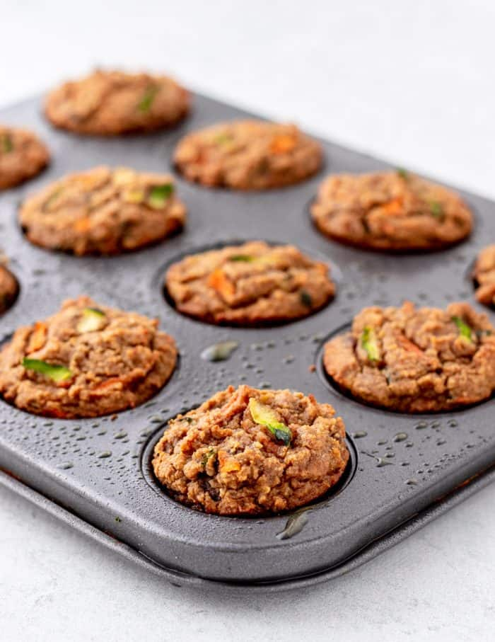 Close up of the baked carrot zucchini muffins in a tin.