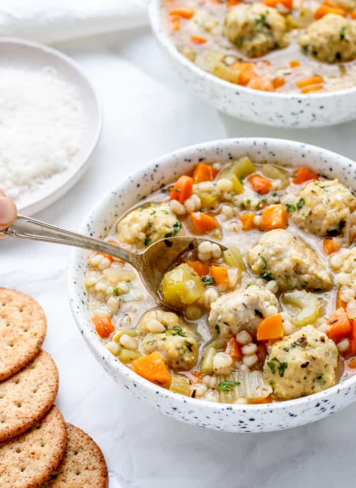 A spoon in a bowl of the Italian chicken meatball soup.