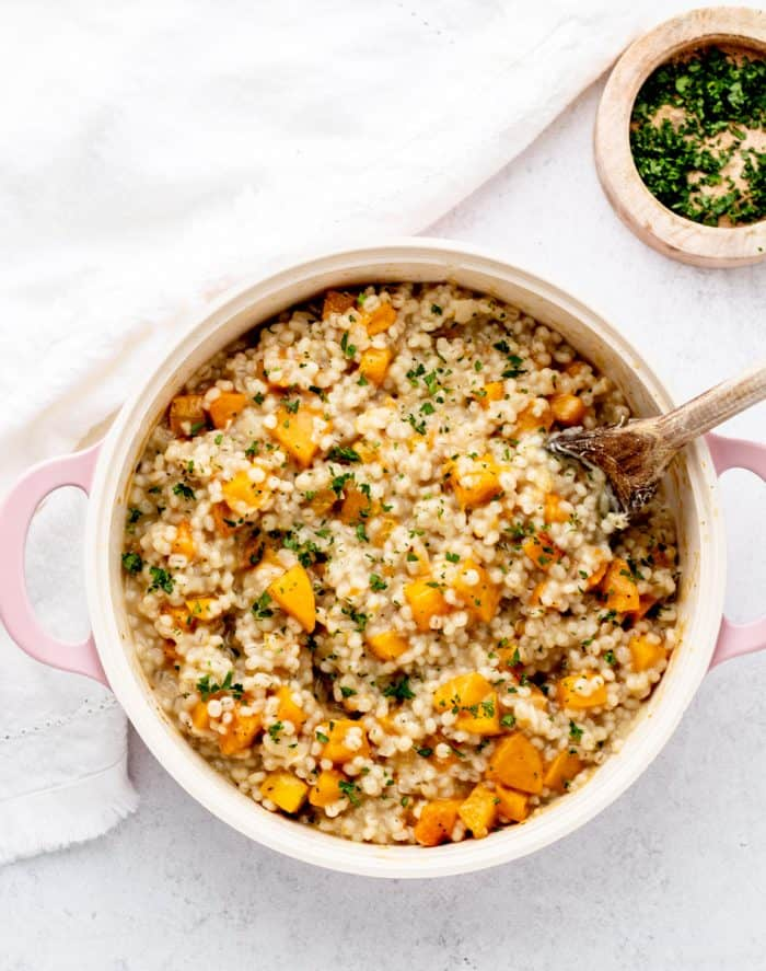 Butternut squash risotto in a large pot with a spoon.