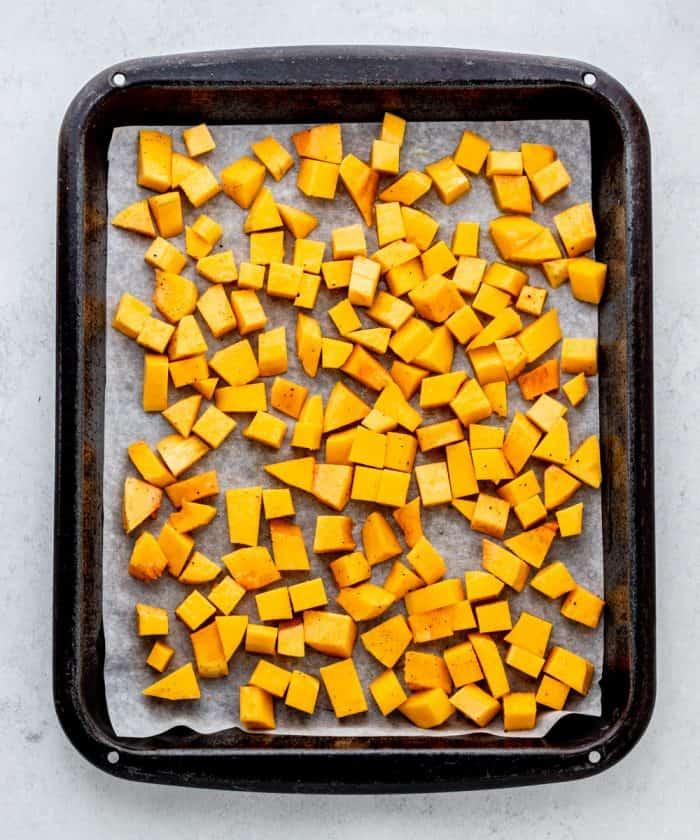 Butternut squash cubes on a baking sheet.