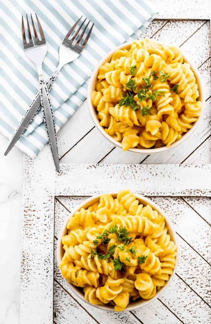 Two bowls of butternut squash mac and cheese topped with parsley