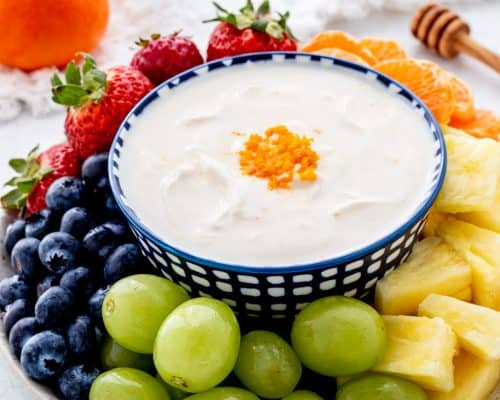A plate of fresh fruit with a bowl of yogurt dip in the middle.