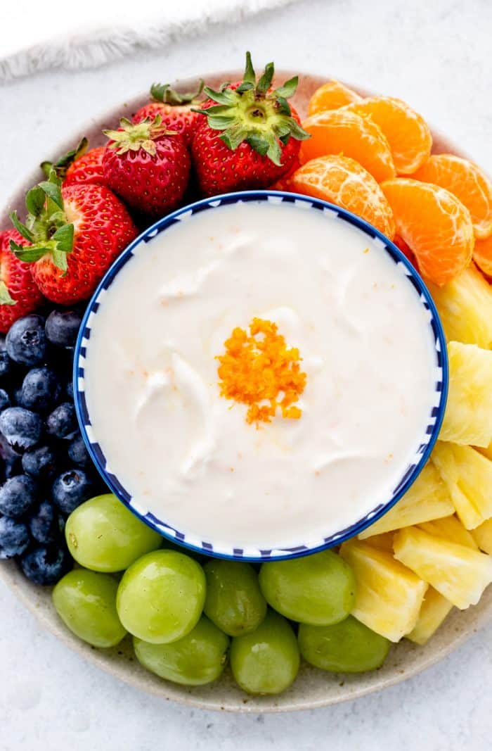 Overhead shot of a fruit yogurt dip in the middle of a platter of fruits.