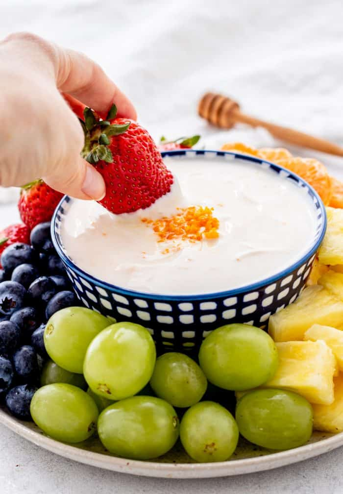 A strawberry being dipped into the yogurt.