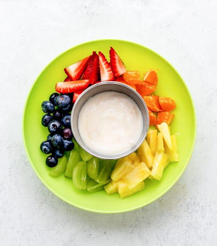 A green plate with chopped fresh fruits and a bowl of Greek yogurt dip.