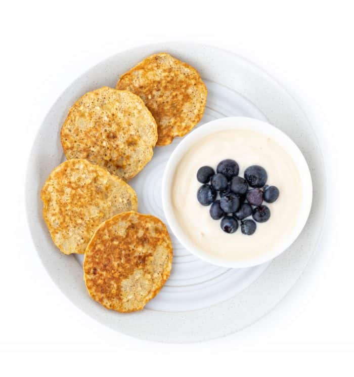 Banana pancakes on a plate with a bowl of yogurt topped with blueberries