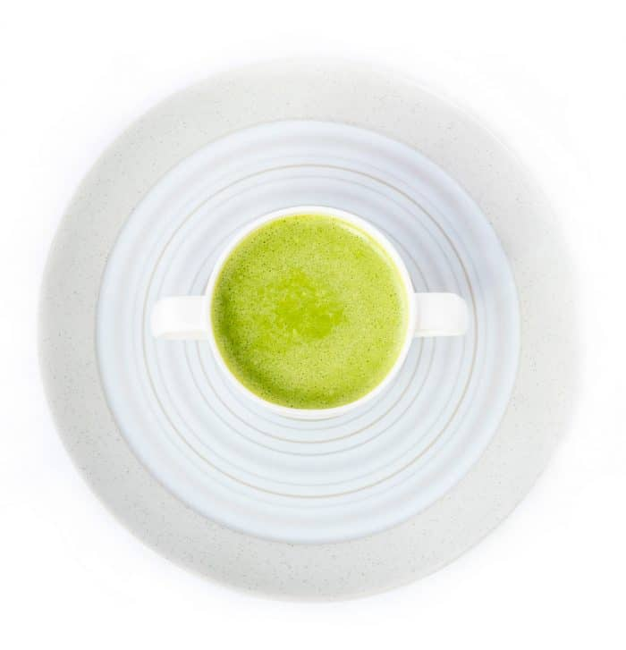 Green smoothie in a cup on a plate