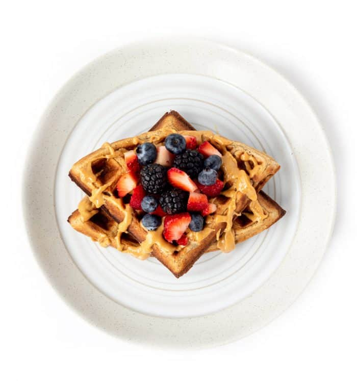 Two waffles on a plate with mixed berries and a drizzle of peanut butter on a plate