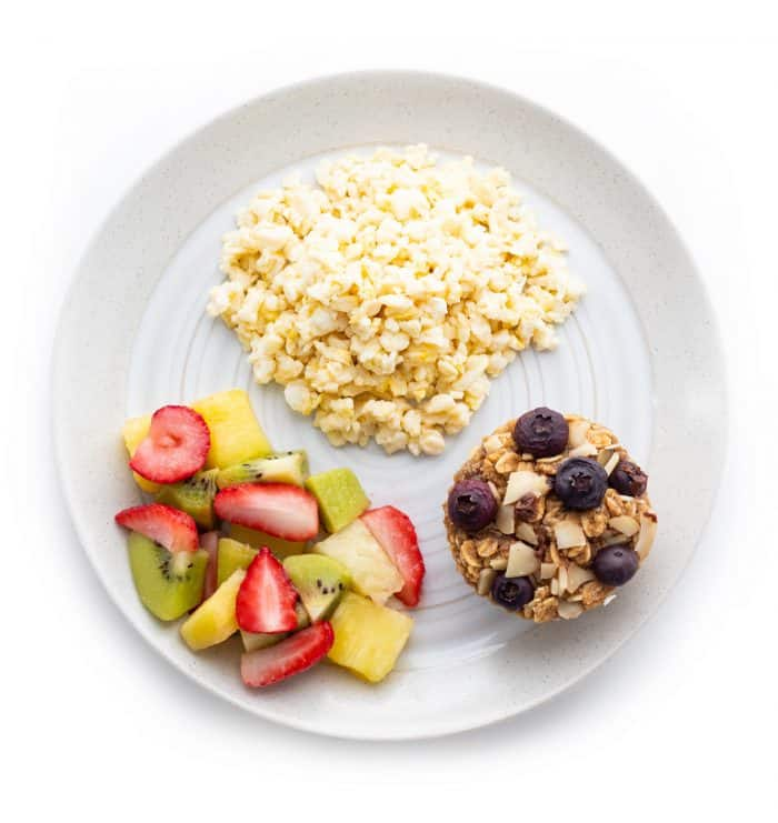 Scrambled eggs with oatmeal muffin and fruit salad on a plate