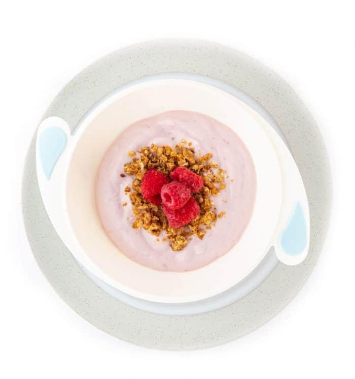 Bowl of yogurt with granola and fresh raspberries on a plate
