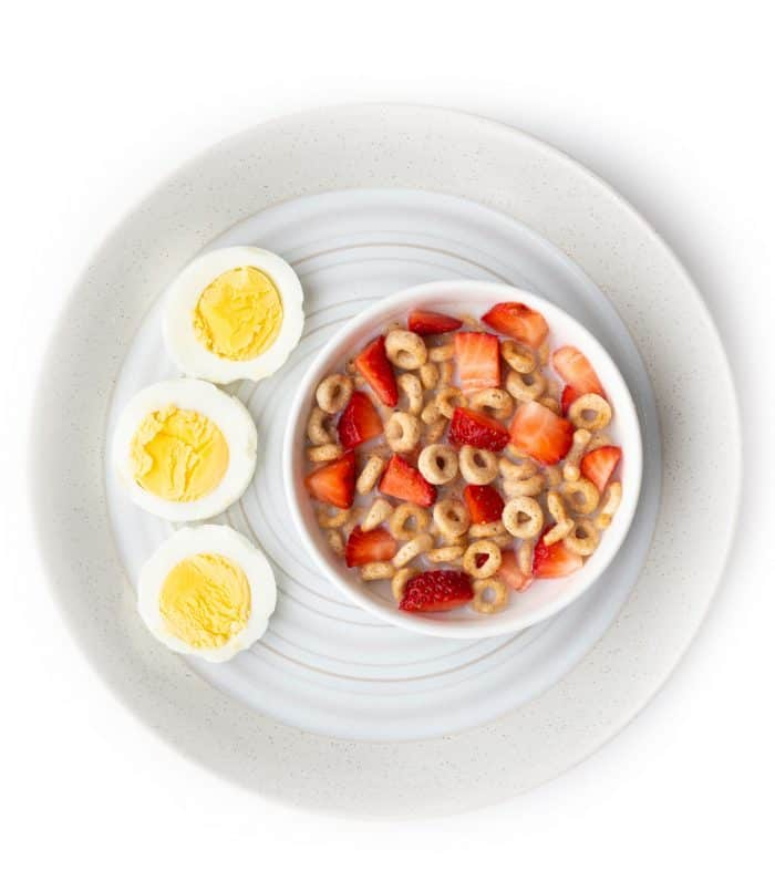 Bowl of cheerios with chopped strawberries and sliced hard boiled egg on a plate