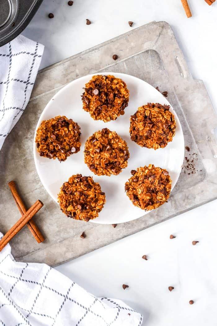 Overhead shot of six pumpkin oatmeal muffins on a white plate.
