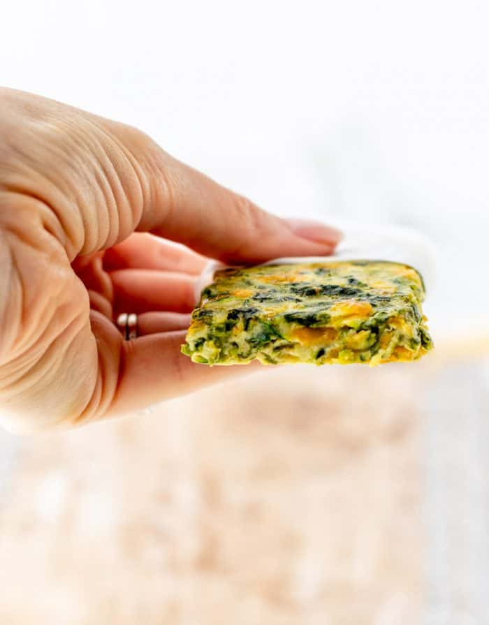 A hand holding a frittata finger.