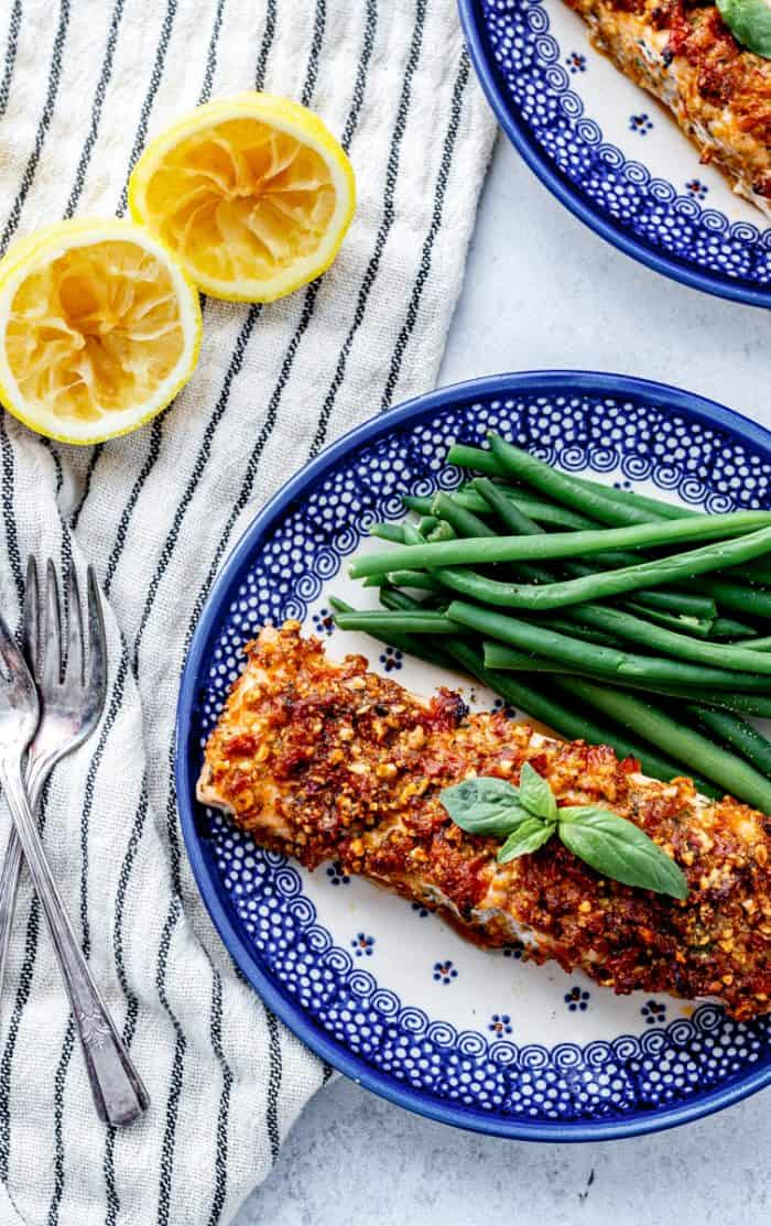 Overhead shot of the pesto crusted salmon served on a blue and white plate.