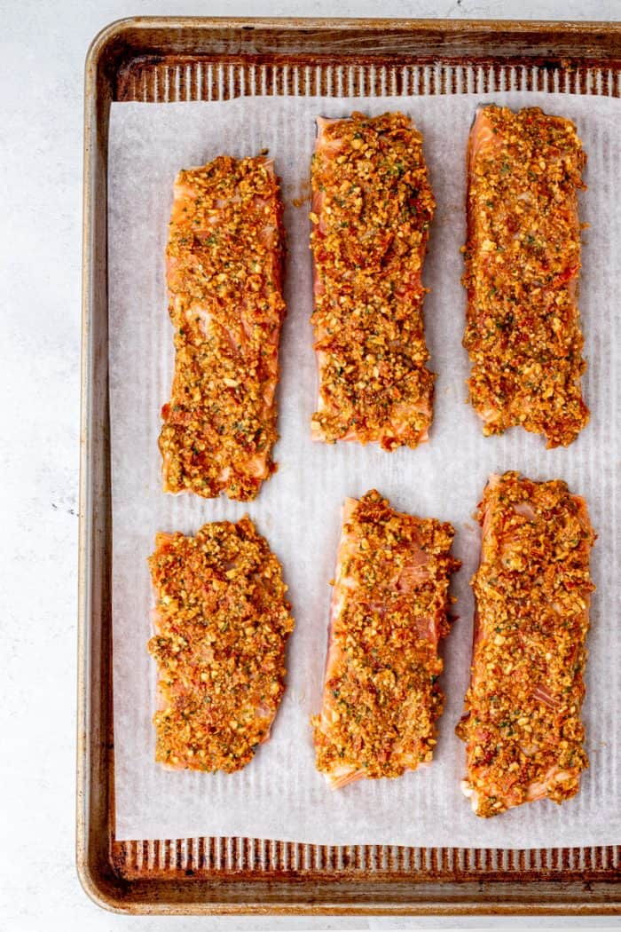Six pesto crusted salmon fillets on a baking sheet.