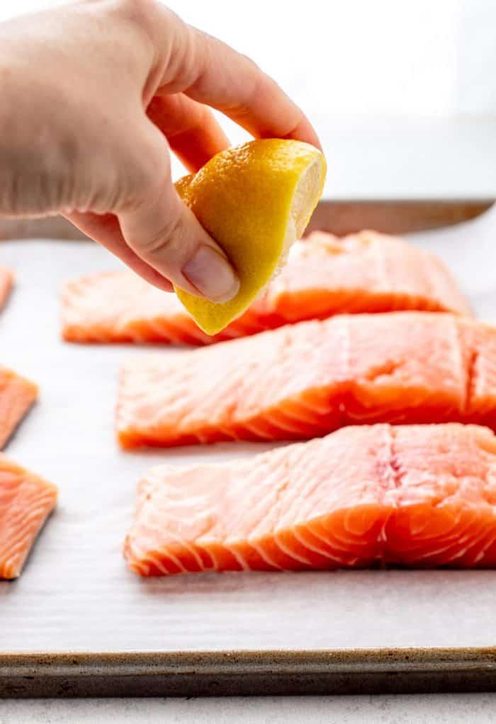 Sqeezing lemon juice over salmon fillets.