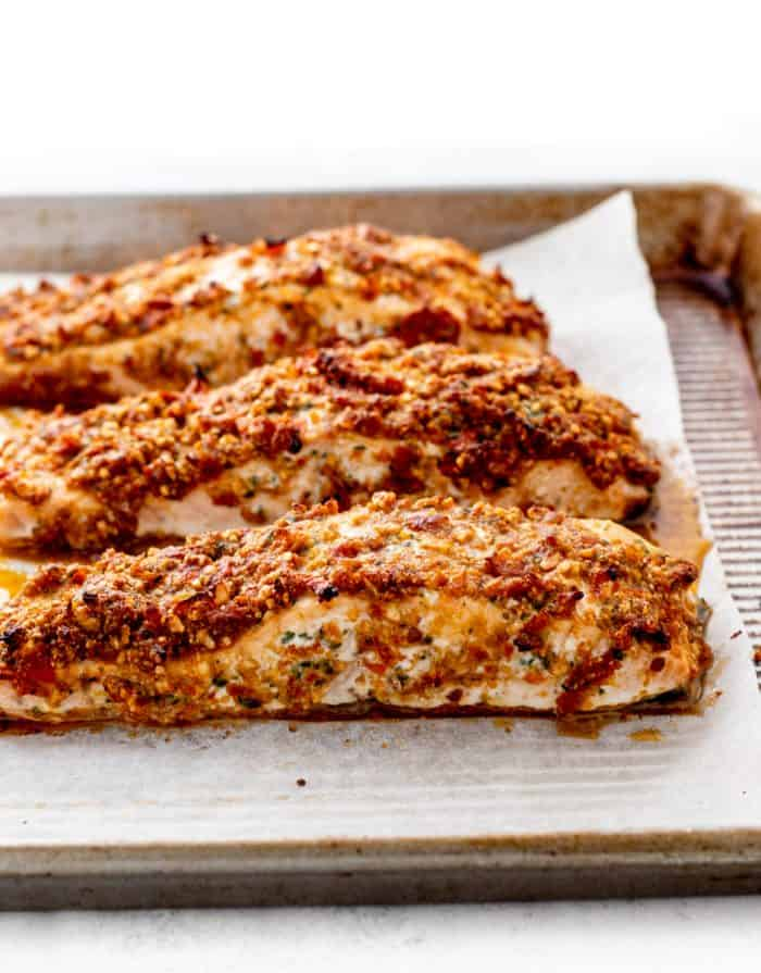 Baked pesto crusted salmon fillets on a baking sheet.