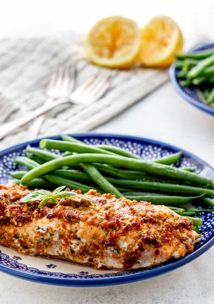 A pesto crusted salmon fillet on a plate with green beans.