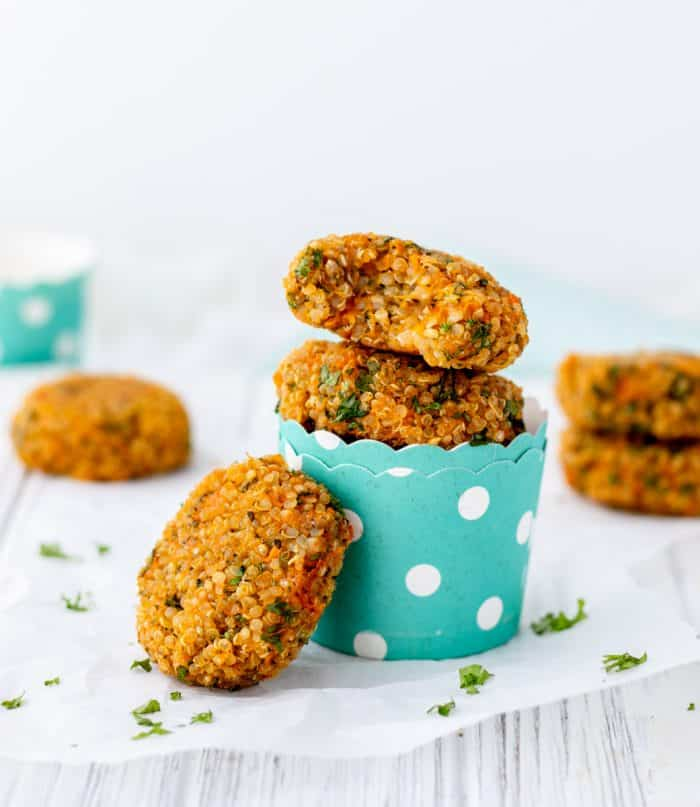 Vegan quinoa patties in turquoise cups with one leaning against the side