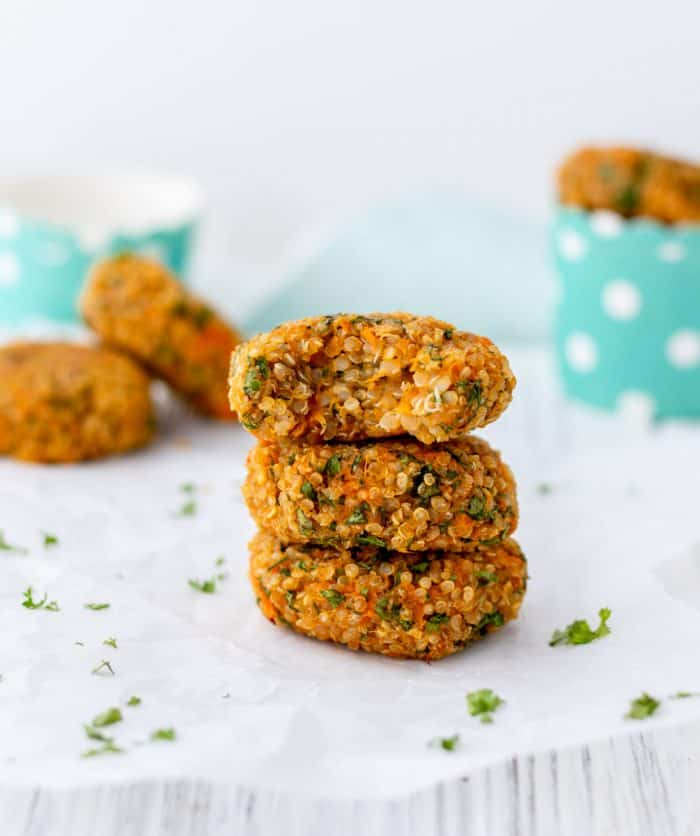 Stack of three quinoa sweet potato cakes with a bite taken out of the top patty