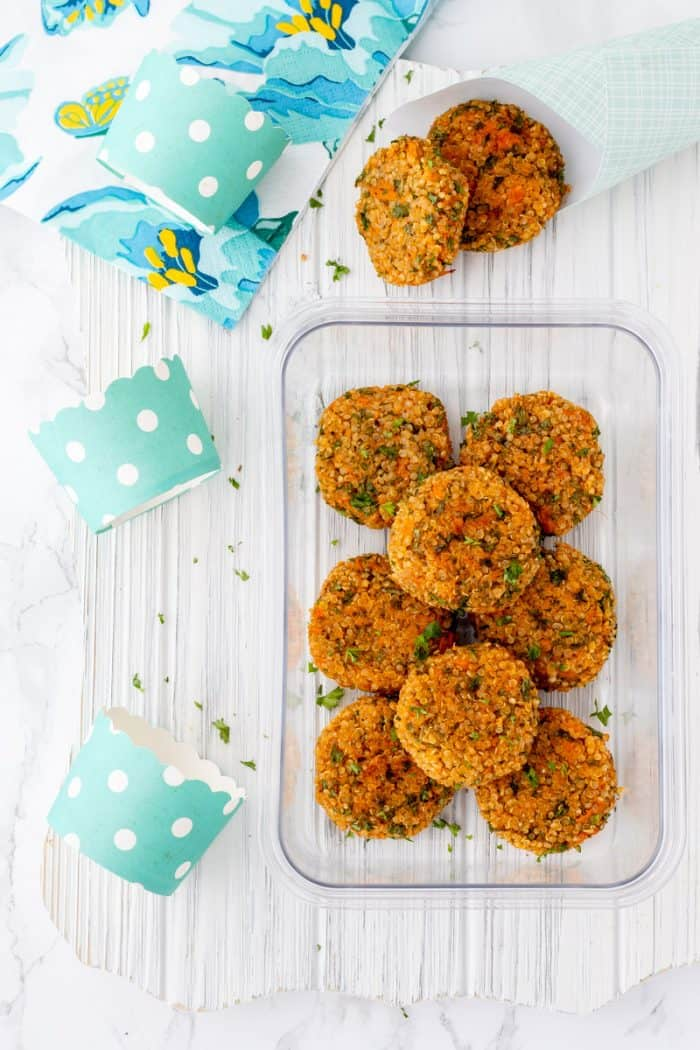 Overhead shot of quinoa cakes in a meal prep container with turquoise polka dot cups and a napkin