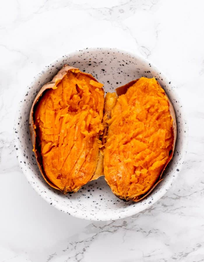 Cooked sweet potato in a bowl on a marble background