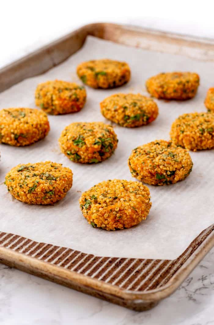 Baked quinoa cakes on a piece of parchment paper on a baking sheet