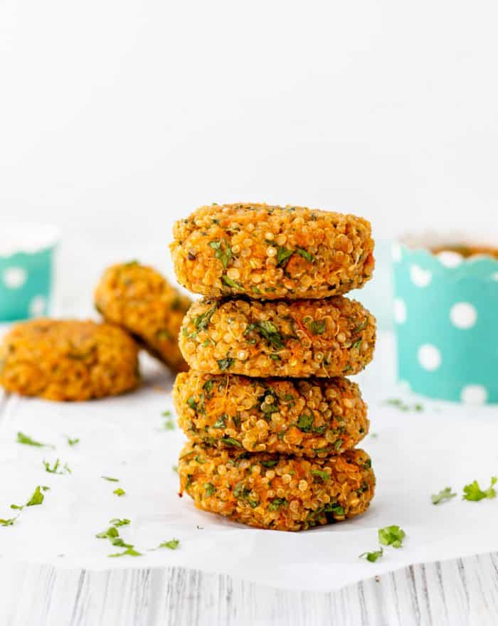 Stack of four quinoa cakes on a white surface with chopped parsley